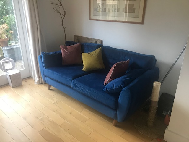 Tidy dining area with blue sofa after home declutter