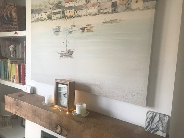 Beautiful coastal wall art and candles bringing a sense of calm